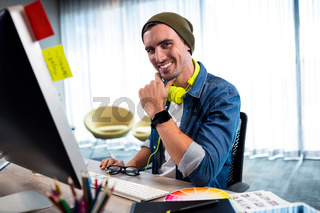 Portrait of smiling casual man working at computer desk