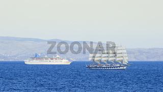Passagierschiff und Windjammer mit Segeln auf hoher See