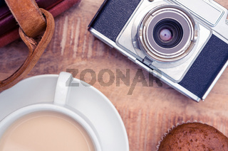 Close-up of old camera with diaries and coffee