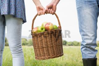 Couple holding basket full of apples