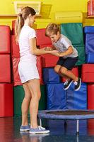 Junge springt auf Trampolin in Turnhalle