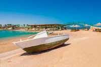 Old fishing boat on sand with blue sky and water