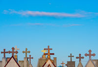 tombstone crosses against blue sky