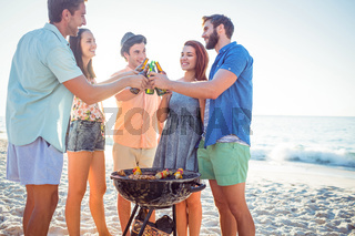 Happy friends doing barbecue and drinking beer