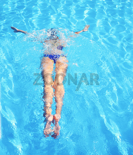Young woman swimming in a blue water of swimming pool