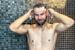 Mann mit Bart wäscht sich die Haare