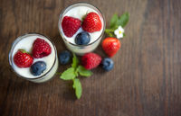 Natural yogurt glasses with fresh berries and mint leaves on Rustic wood
