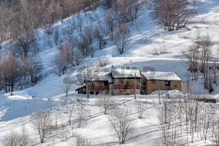 Stone house on snowy slope in Italy.