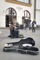 Busker playing guitar at the front of Hard Rock Cafe in Krakow