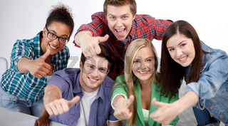 group of happy students showing thumbs up