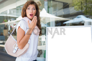 Portrait of surprised woman standing next to a blank board