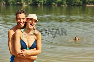 Paar am See und Tochter beim Baden