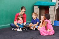 Frau liest Buch vor für Gruppe Kinder