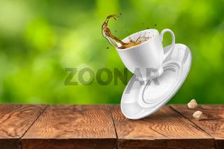 Splash of tea on wooden table against green background