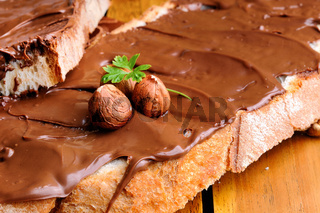 Bread with chocolate cream and hazelnuts on a table closeup