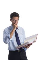 Pensive businessman with file folders in hand