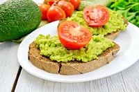 Sandwich with guacamole avocado and tomato on light board