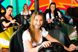 Beautiful girls in an electric bumper car in amusement park