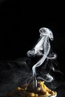 White candle smoke at dark background