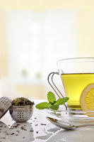 Green tea with mint and lemon with strainer vertical composition