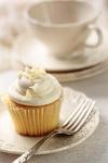Closeup of vanilla cupcake with tea cup