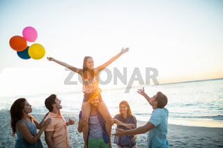 Happy friends dancing on the sand with balloon