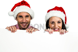 Festive couple showing a sign