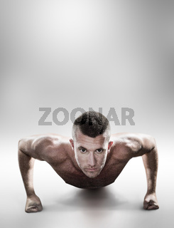 Composite image of portrait of confident shirtless man doing push ups