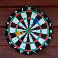 Used dartboard with two darts over wooden background.
