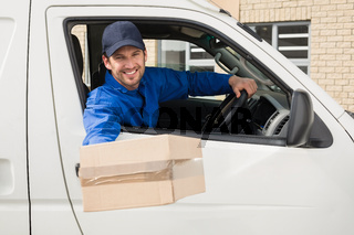 Delivery driver offering parcel from his van