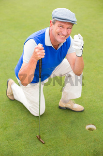 Smiling golfer kneeling on the putting green