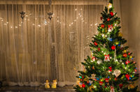 Decorated Christmas tree with Santa and gifts in interior