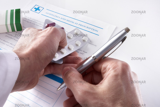 Doctor writing down a medical prescription elevated view