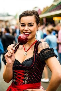 Attractive young woman with love apple at the Oktoberfest