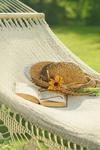 Straw hat and book on lace hammock