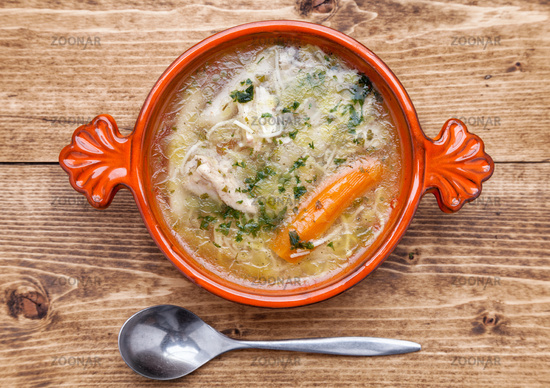 Fresh and healthy chicken soup with vegetables on wooden background