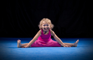 Little girl doing gymnastic exercises on black