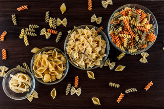Pasta on dark wooden background in glass dishes close-up macro