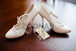 white bridal shoes with earrings on wooden table