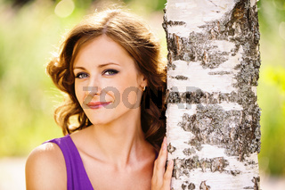cute dark-haired woman near birch tree