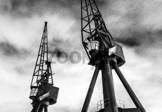 Royal Victoria Dock disused industrial cranes at night in black and white, Docklands, London, United Kingdom