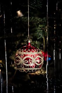Rot glänzende Christbaumkugel mit goldenem Muster am Weihnachtsbaum