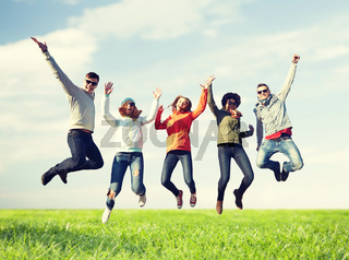 smiling friends in sunglasses jumping high