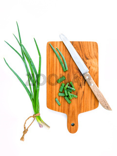 Branch of fresh spring onions and spring onions chops with cutting board and knife for seasoning concept isolated on white background.