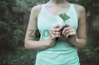 Woman holding Ginkgo biloba leaf in her hand