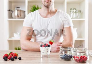 Healthy eating concept. Closeup on man with delicious yoghurt with fresh berries