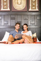 Young couple using a Tablet PC in a asian hotel room