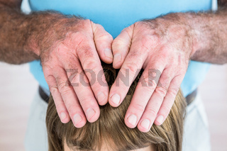 Male hands performing reiki over woman