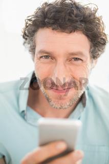 Smiling casual businessman sending a text