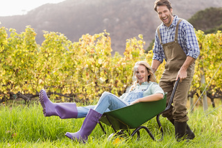 Happy couple in dungarees pushing a wheelbarrow